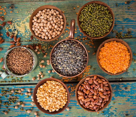 legume: Raw legume on old rustic wooden table, close-up. Stock Photo