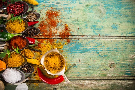 variety: Various colorful spices on wooden table, top view.