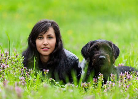 black dog: Beautiful Brunette woman with black dog posing on spring meadow. Stock Photo