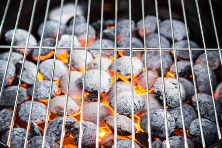 briquettes: Empty grill with red-hot briquettes, close-up.