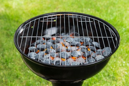 lawn party: Empty grill with red-hot briquettes, close-up.