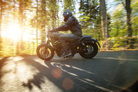 motor bike: Man seat on the motorcycle on the forest road during sunrise.