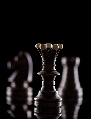 Chess pieces on black background, close-up.