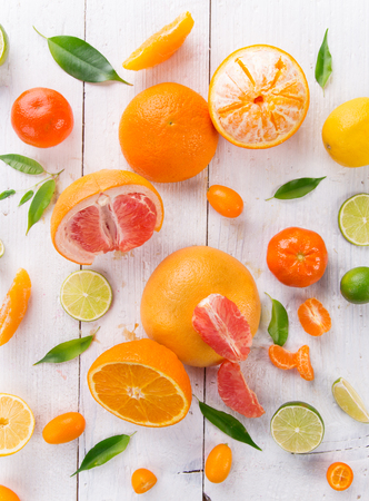 assorted: Citrus fresh fruits on a wooden table, close-up.