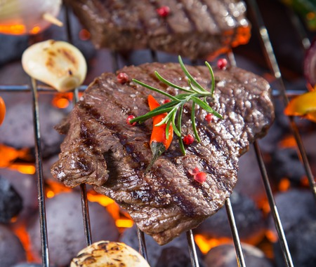 dinner party: Assorted delicious beef steaks with vegetable on a barbecue grill.