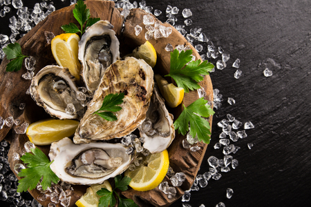 ice crushed: Fresh oysters on a black stone plate top view