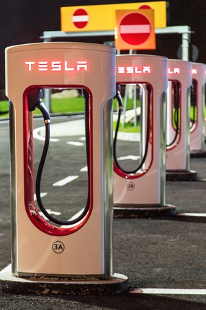 voltage gray: BRENNER, AUSTRIA - MAY 11, 2016: Tesla supercharger machine at Supercharger Station at night.