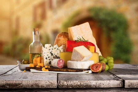 scamorza: Delicious cheeses on old wooden table, close-up. Stock Photo