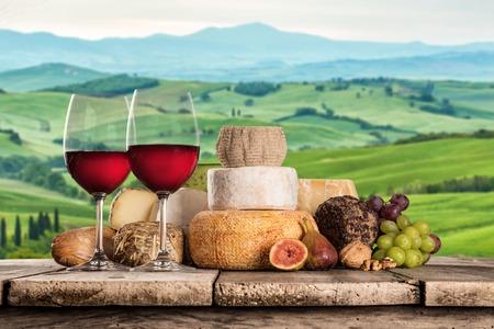 古い木製のテーブルの上の赤のワインと美味しいチーズ クローズ アップ。 写真素材