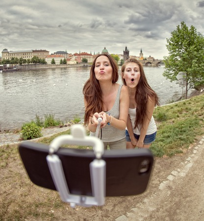sticking: Friends making selfie. Two beautiful young women making selfie and grimacing