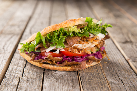 close up of kebab sandwich on wooden background