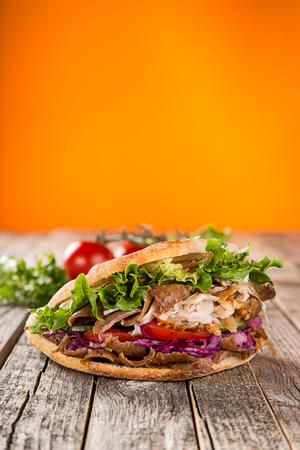 木製の背景のケバブ サンドイッチのクローズ アップ