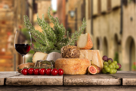 scamorza: Delicious cheeses with red wines on old wooden table, close-up.