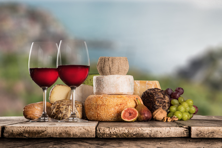 caciocavallo: Delicious cheeses with red wines on old wooden table, close-up.