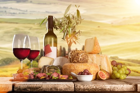italian landscape: Delicious cheeses with red wines on old wooden table, close-up.