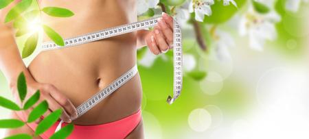 abdomen plano: Una muchacha delgada que mide su cintura, primer plano.
