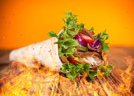 close up of kebab sandwich on wooden background with fire flames. Stock Photo