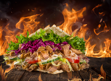 close up of kebab sandwich on wooden background with fire flames.