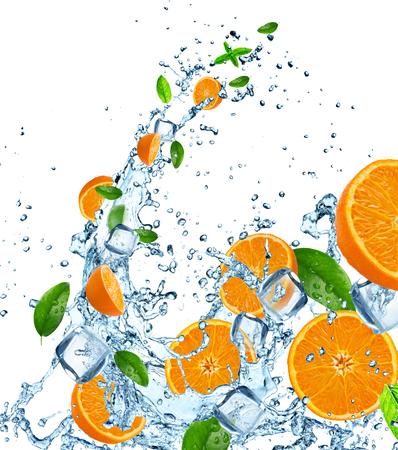 Fresh oranges in water splash over white, close-up.