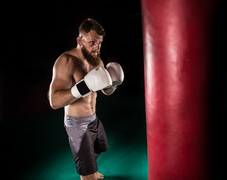 forceful: Muscular hipster fighter giving a forceful kick during a practise with a boxing bag. Kickboxing.