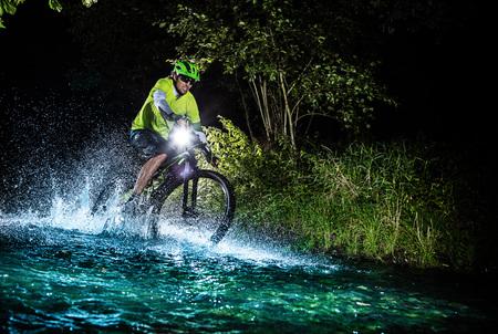 summer sport: Mountain biker speeding through forest stream. Water splash in freeze motion. Night ride. Stock Photo