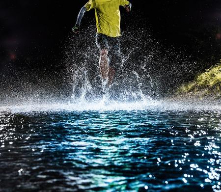 sports race: Single runner running, making splash in a stream during night.