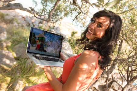 Beautiful young brunette woman with notebook. Summer sunny day with olive tree. Stock Photo