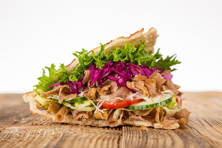 roast meat: close up of kebab sandwich on white background