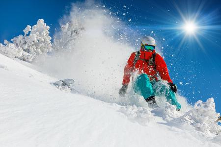 Skifahrer Skifahren bergab im sonnigen Tag in den hohen Bergen