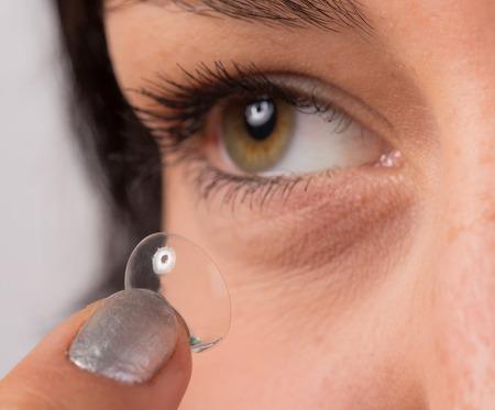 wearer: Young woman putting contact lens in her eye. Macro shot.