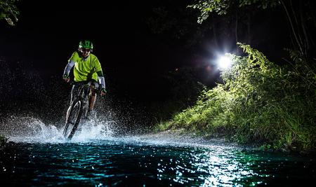 mountain biker: Mountain biker speeding through forest stream, water splash in freeze motion.