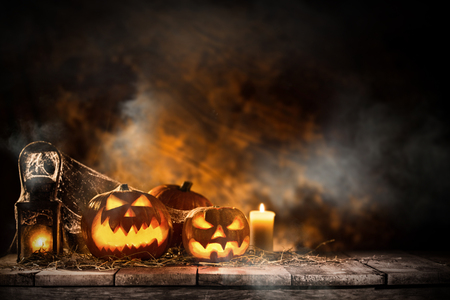wood carvings: Halloween Pumpkins on old wooden table Stock Photo