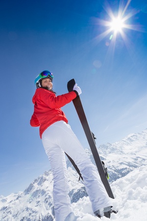 Beautiful young woman with ski in high mountains.