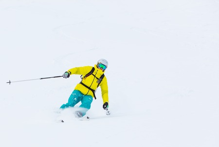 piste: Skier skiing downhill in high mountains during sunny day.