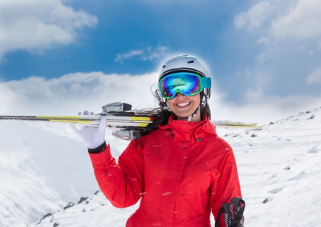 respite: Beautiful young woman with ski in high mountains.