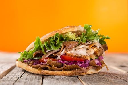 Cerca de sándwich de kebab en el fondo de madera Foto de archivo - 68076174