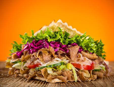 sandwich de pollo: close up of kebab sandwich on wooden background