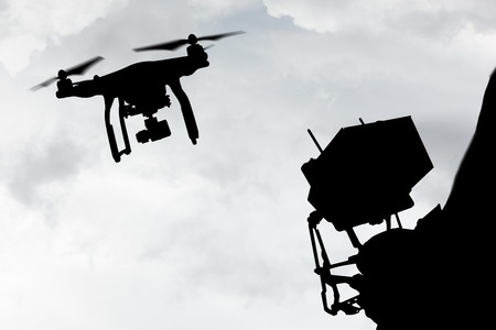 Drone quad copter with high resolution digital camera flying in the blue sky.