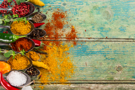 Various colorful spices of the world on wooden table, close-up. Stock Photo