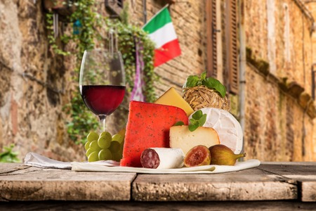 caciocavallo: Delicious cheeses with wine on old wooden table. Stock Photo