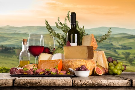 Delicious cheeses with wine on old wooden table. Standard-Bild