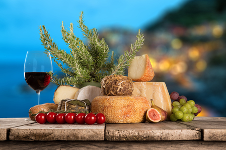 Delicious cheeses with wine on old wooden table. Stock Photo