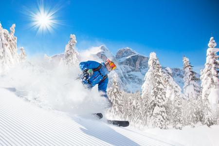Skiërs skiën omlaag in hoge bergen