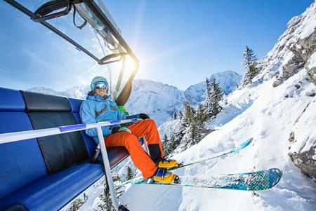lift: Skier sitting at ski lift.