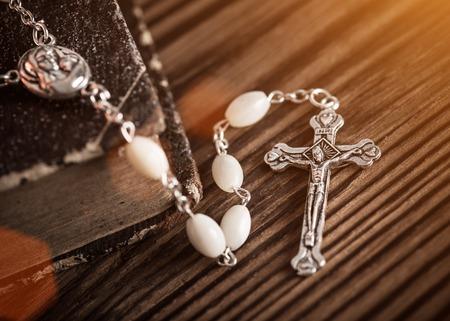 baptized: Closeup of iron Christian cross with holy Bible.
