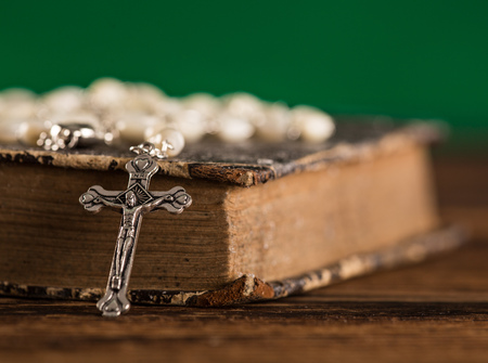 hymn: Closeup of iron Christian cross with holy Bible.