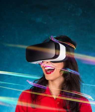 virtual reality simulator: Happy woman with glasses of virtual reality. Stock Photo