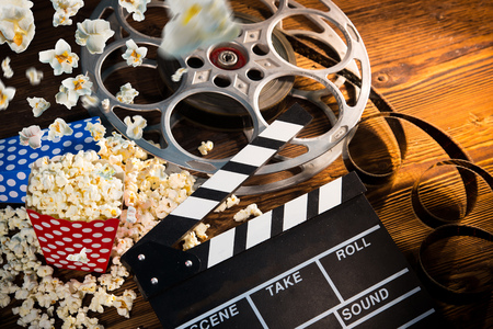 cinema film: Cinema concept of vintage film reel with popcorn.