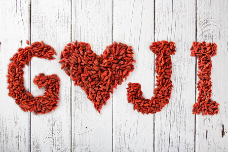 Goji berries as a heart and letters on old white wooden table. Stock Photo