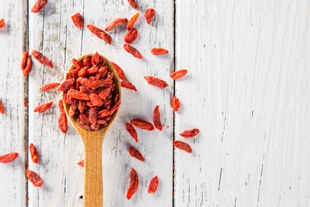 Dry goji berry on old white wooden background. Stock Photo
